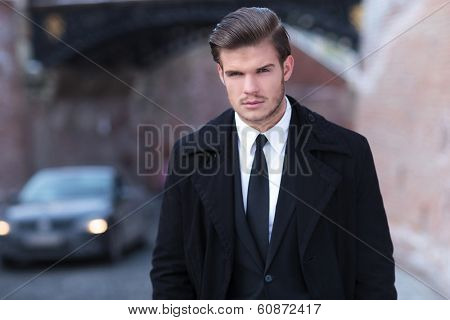 portrait of an elegant young business man posing outdoor, wearing an overcoat and looking into the camera