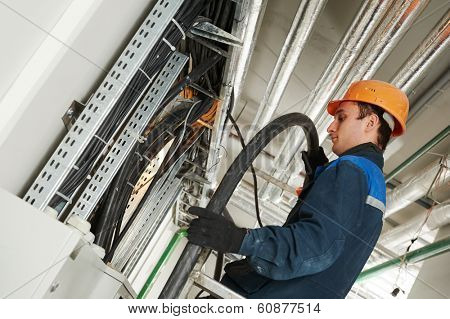 electrician builder engineer installing industrial cable into fuse box