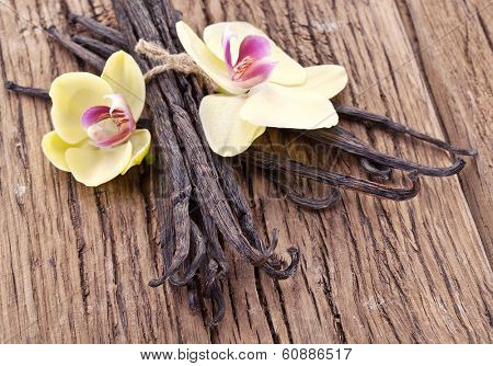 Vanilla sticks with a flower on a wooden table.