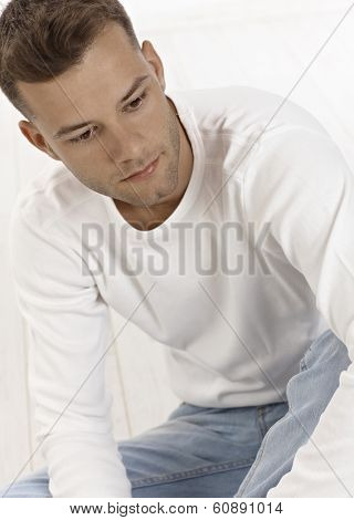 Portrait of daydreaming young man sitting on floor, looking away.