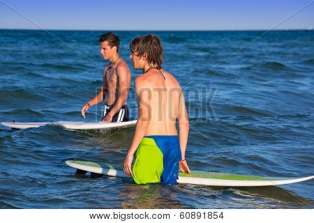 boys surfers waiting for the waves on the blue beach