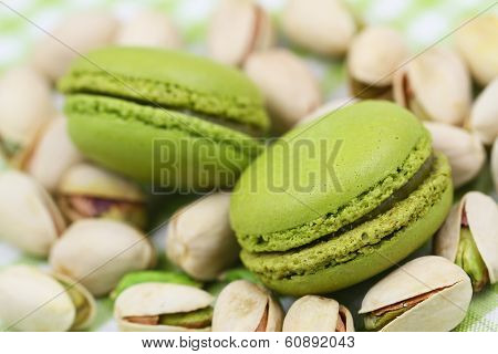 Pistachio macaroons on pistachio nuts, close up