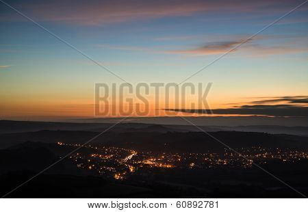 Pre-sunrise Landscape Overlooking Brightly Lit Town In Valley In Winter