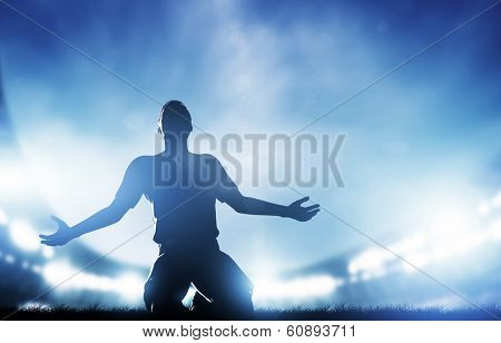 Football, soccer match. A player celebrating goal, victory. Lights on the stadium at night.