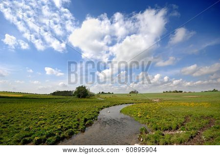 Small river, framland and blue and cloudy sky.