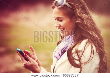 smiling woman with  reading message on smart phone outdoor shot retro colors