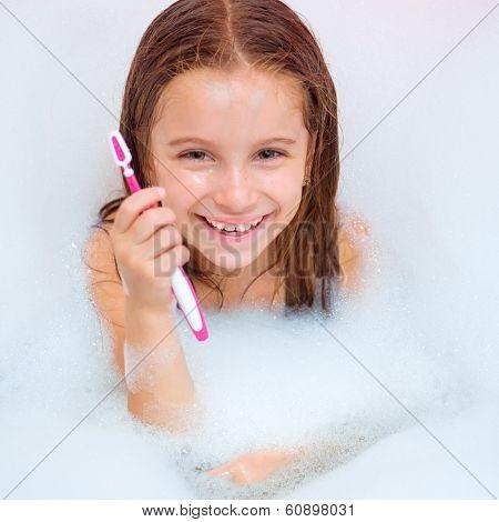 Cute girl brushing teeth in bath