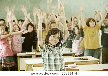 Cheerful group of kids at school room having education activity