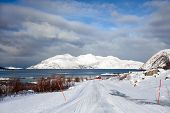 foto of tromso  - Winter landscape in Troms county Norway : desert road leading to a fjord surrounded by snowy mountains