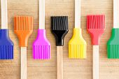 stock photo of baste  - Colorful line of kitchen brushes in the colours of the rainbow for decorating and glazing pastries or basting meat arranged in an alternating pattern on a wooden background - JPG