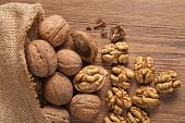 stock photo of arabian  - Walnut kernels and whole walnuts on rustic old wooden table - JPG