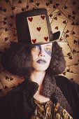stock photo of jester  - Vintage textured portrait of a poker cards jester woman with creative makeup and old hairstyle wearing the card of hearts on top hat - JPG