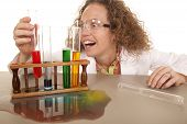 stock photo of bulge  - A crazy woman scientist with some test tubes full of colored liquid - JPG