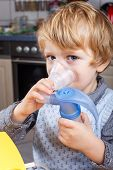 picture of inhalant  - Adorable toddler boy making inhalation with nebulizer and inhalator in home kitchen - JPG