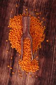 picture of legume  - Red lentils on wooden spoon on dark wooden background - JPG