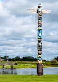 foto of indian totem pole  - Totem Pole standing next to a lake with a cloudy sky - JPG