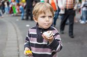 foto of funfair  - Little boy of three years eating sweets at a funfair outdoors - JPG