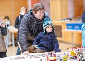 stock photo of exposition  - Father and little son having fun on toy exposition indoors - JPG