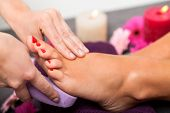 stock photo of pumice-stone  - Woman having a pedicure treatment at a spa or beauty salon with the pedicurist massaging the soles of her feet with a pumice stone to cleanse dead skin and stimulate the tissue