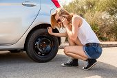 stock photo of frown  - Attractive young blond woman inspecting her car engine after a breakdown at the roadside frowning in annoyance and frustration - JPG