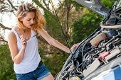 image of frown  - Attractive young blond woman inspecting her car engine after a breakdown at the roadside frowning in annoyance and frustration - JPG