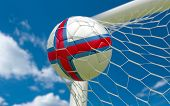 stock photo of faro  - Faroe Islands flag and soccer ball football in goal net - JPG