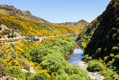 stock photo of ravines  - Train and coaches of Taieri Gorge tourist railway runs alongside river in a ravine on its journey up the valley - JPG