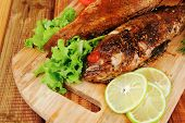 healthy food: two fried sea bass fish served with tomatoes and vegetables on big wooden board over t