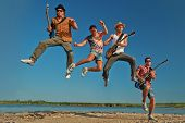 Four men with guitars jumping on the river.