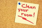 Clean your room yellow sticker pined on the corkboard