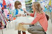 pic of supermarket  - woman and little girl choosing and trying on dress clothes during shopping at garment supermarket - JPG