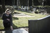 picture of deceased  - Woman on graveyard sitting at grave of deceased relative. Sad, mourning.