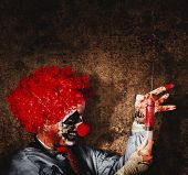 stock photo of freaky  - Evil halloween clown with big scary needle performing sinister healthcare practise on dark grunge background - JPG