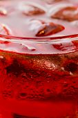Refreshment: Bubble, Fizz And Ice In A Glass In A Red Liquid
