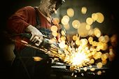 stock photo of welding  - Industrial worker cutting and welding metal with many sharp sparks - JPG