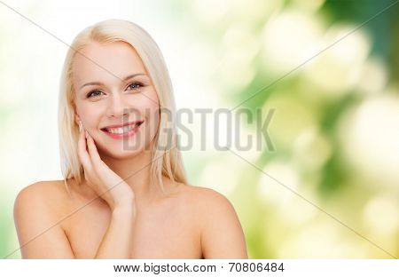 health and beauty concept - smiling young woman touching her face skin