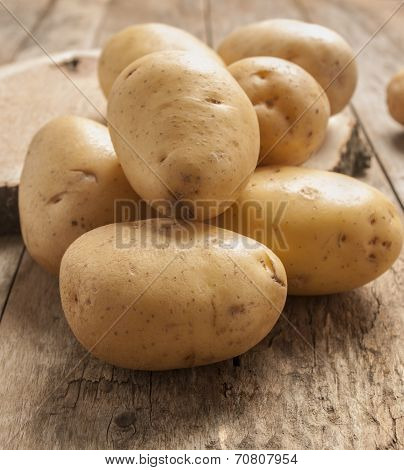 fresh potatoes close up on wooden table