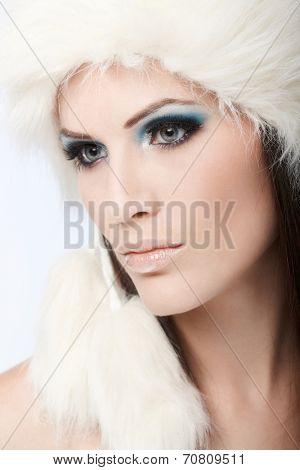 Closeup portrait of beautiful winter girl in fancy makeup and white fur cap.
