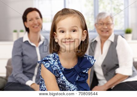 Portrait of beautiful little girl smiling happily. Mother and granny at background.