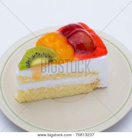 Piece Of Cake With Fresh Fruit Isolated On White Background.