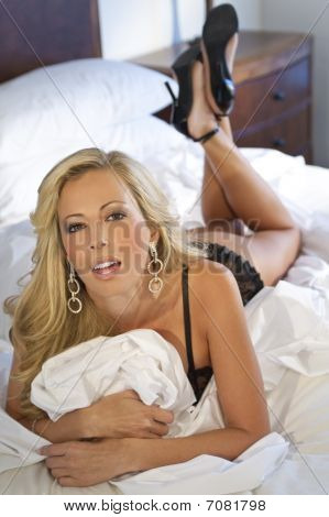 Beautiful Blond Woman On Bed In Black Lingerie And Heels