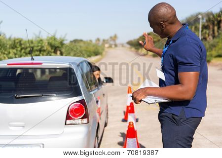 african instructor teaching learner driver to park a car in testing ground