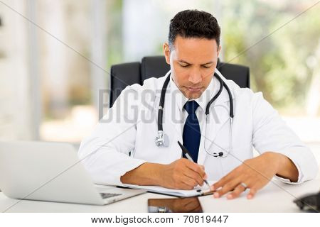male medical doctor writing reports in his office