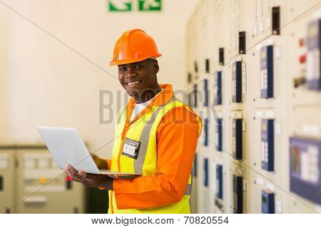 african electrical engineer using laptop computer in power plant control room