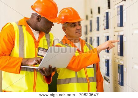 two professional electricians checking industrial control box