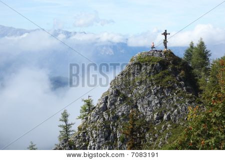 Rock Climber Drinking Near Christian Cross In Front Of Panorama
