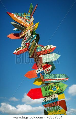Many colorful wooden direction signs to far locations