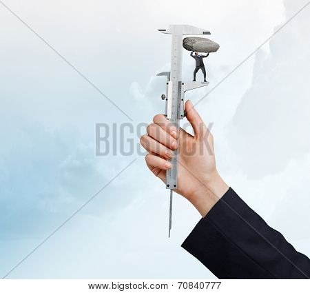 Close up of male hand pressing miniature of businessman