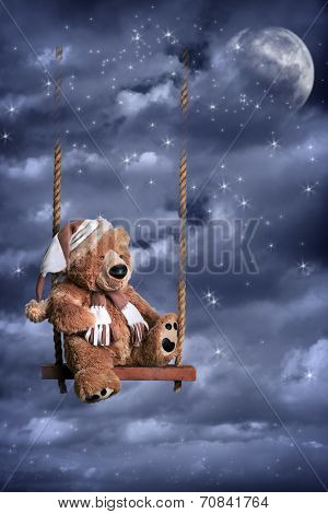 Teddy bear on swing against a night sky with moon and stars