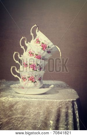 Stack of tilted vintage teacups with milk spilling out